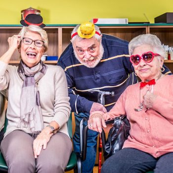Retired Adults wearing gag gifts and laughing